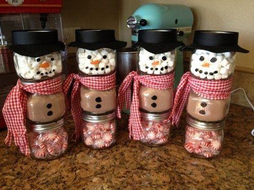 Bonhomme de neige dans des pots avec chocolat et bonbons,