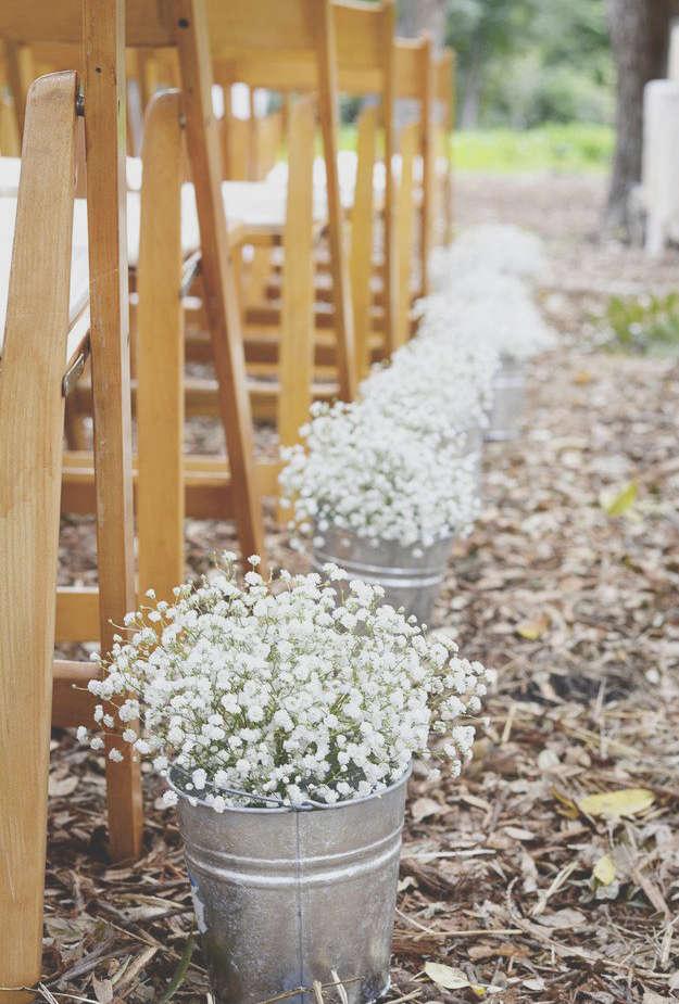 pots avec des fleurs pour décorer l'allée de mariage